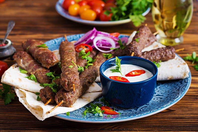 Kebab adana, chicken, lamb and beef on lavash bread with sauce. stock photo