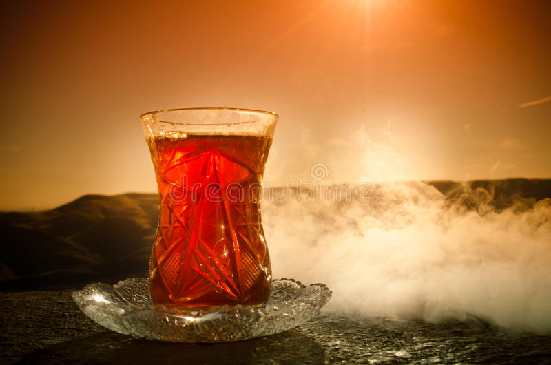 Turkish Azerbaijan tea in traditional glasse and pot outdoor nature background with sunlight and smoke. Eastern tea concept. Armud. U traditional cup. Sunset royalty free stock images