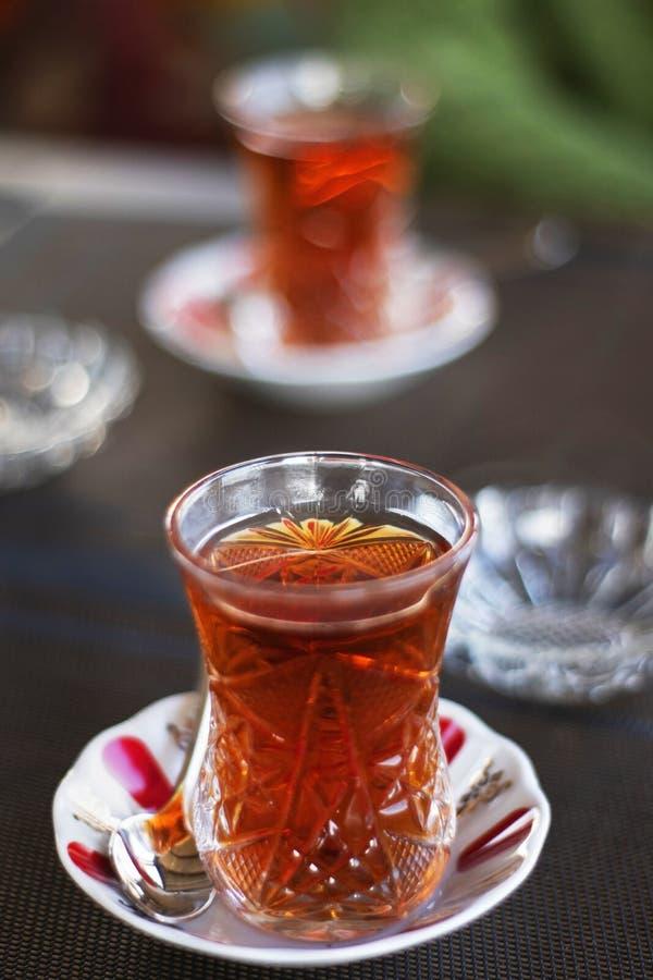 Turkish or Azerbaijani tea in pear shape glasses Armudu on a table cloth, traditional eastern hot black tea for Ramadan or Novru royalty free stock image