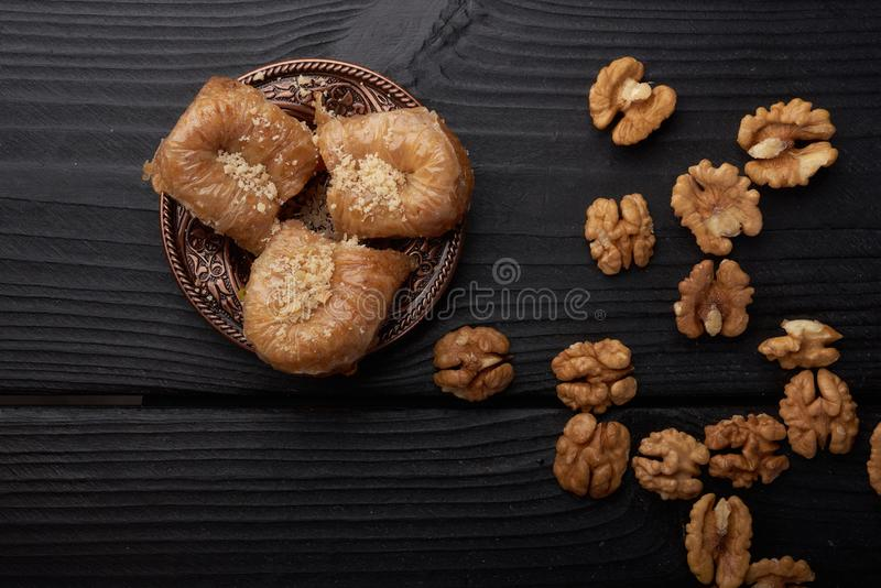 Turkish baklava near walnuts on black wooden background royalty free stock photos