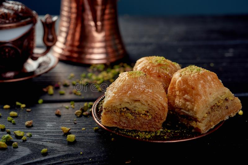 Turkish baklava near walnuts on black wooden background royalty free stock image