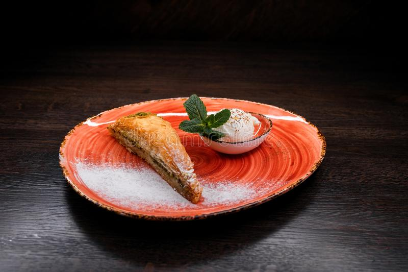 Turkish baklava with pistachios and vanilla sweet ice cream decorated with fresh mint leaves. Traditional Oriental cuisine. stock image