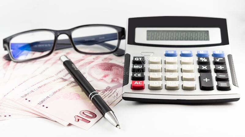 Turkish banknotes, glasses, pen and calculator on white background stock photography