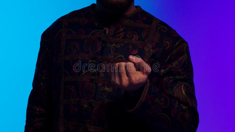 Turkish bearded young man in national costume opening slowly his palm and showing black, round coin. Stock. Turkish man. Turkish bearded young man in national stock photos