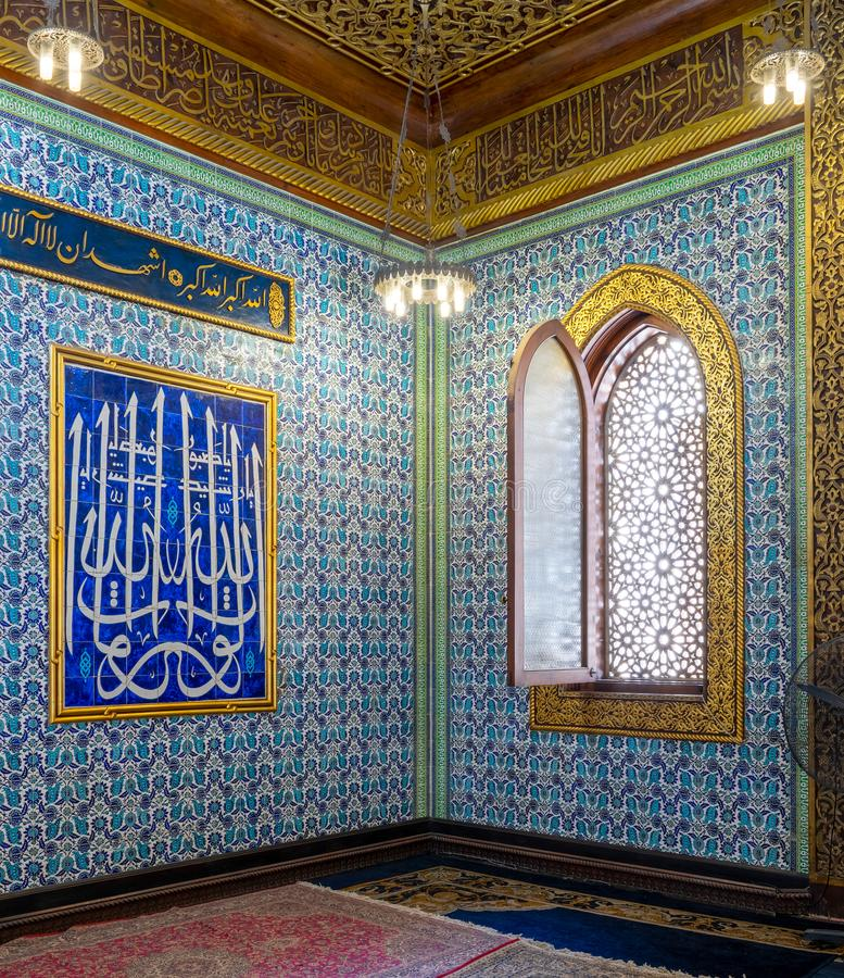 Turkish blue floral pattern ceramic tiles wall with decorated window and calligraphy moral, Mosque at Manial Palace, Cairo, Egypt. Turkish blue floral pattern royalty free stock images