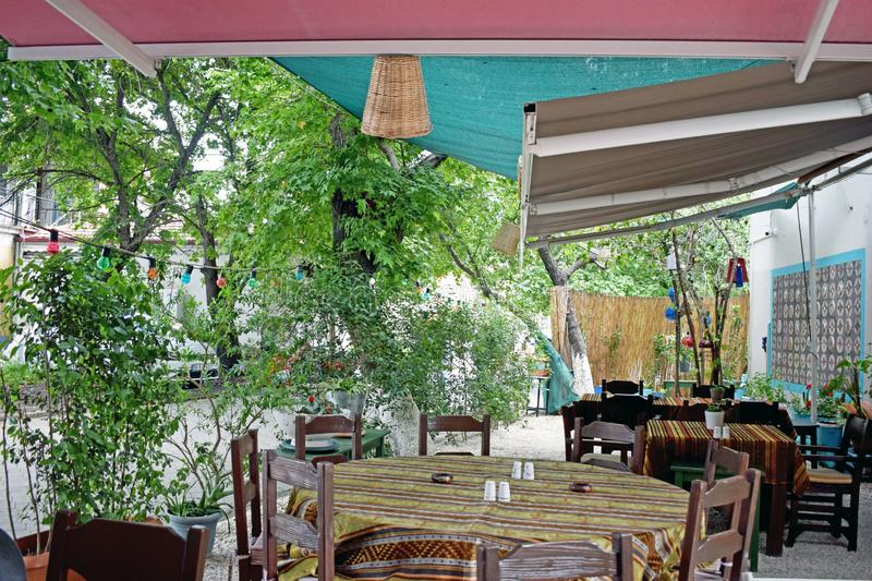 A Turkish cafe. Turkish cafe with patterned table clothes and slat and pepper pots on the tables ,wooded chairs around and plants growing by the side stock image