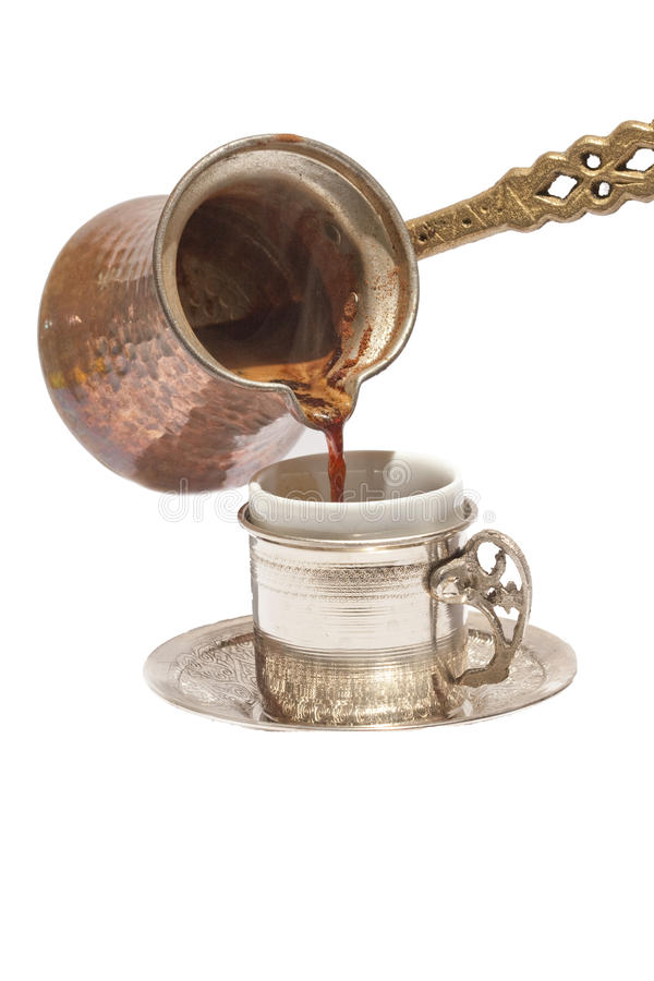 Turkish Coffee. A Turkish coffee is being poured into its original cup on an isolated white background royalty free stock images