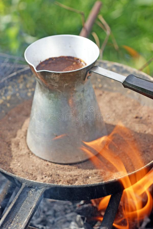 Turkish coffee in cezve prepared on a pan with hot sand. Traditional turkish coffee in cezve prepared on a pan with hot sand burning coals stock image