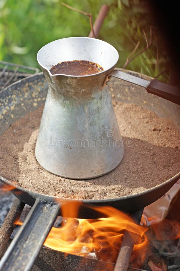 Turkish coffee in cezve prepared on a pan with hot sand. Traditional turkish coffee in cezve prepared on a pan with hot sand burning coals royalty free stock photography