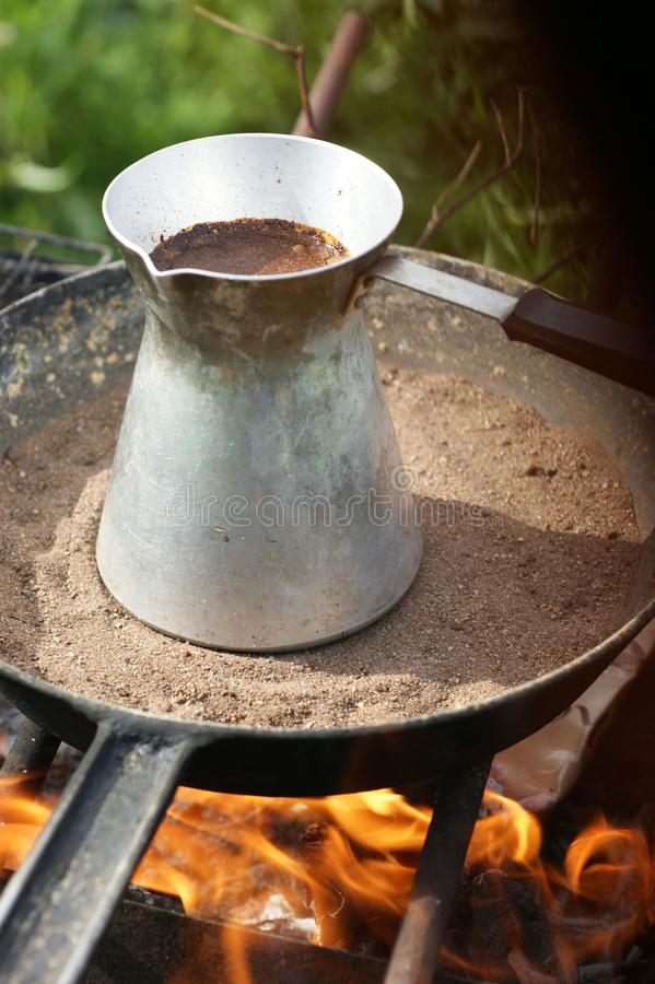 Turkish coffee in cezve prepared on a pan with hot sand. Traditional turkish coffee in cezve prepared on a pan with hot sand burning coals royalty free stock image