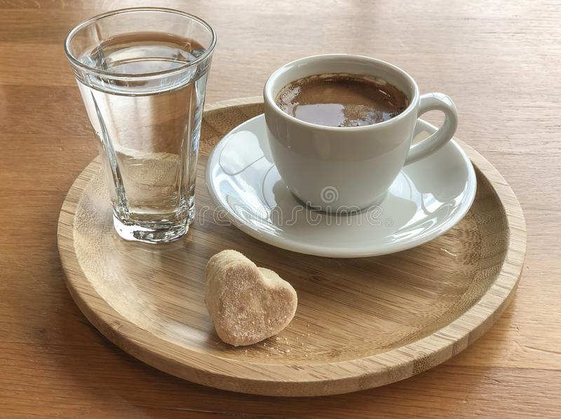 Turkish coffee and water served with a cookie royalty free stock image