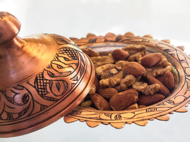 Turkish copper candy bowl handmade with embossing and national pattern stands on a glass table, filled with walnuts and almonds royalty free stock photo