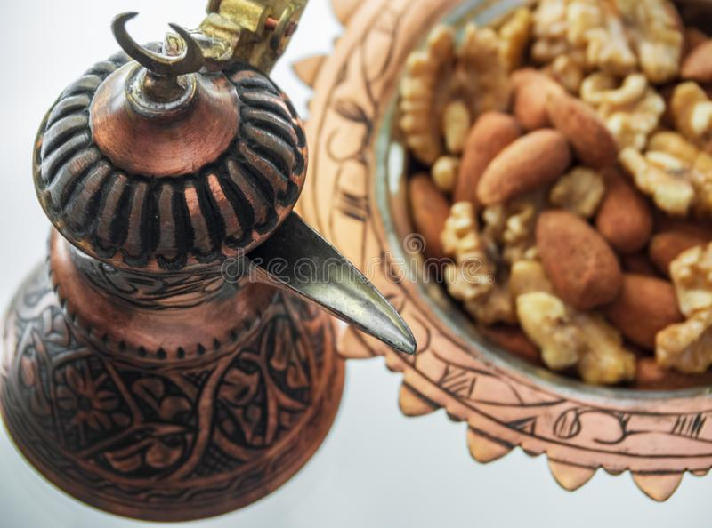 Turkish copper cookware handmade from Turks and candy dish with almonds and walnuts. Turkish copper cookware handmade from Turks and candy dish with almonds  and royalty free stock photo