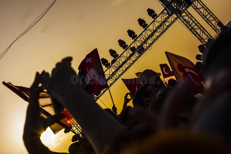 Turkish crowd in the sunset commemorating liberation from greeks. A crowd of people is waving many turkish flags in the sunset in Izmir to commemorate the royalty free stock image