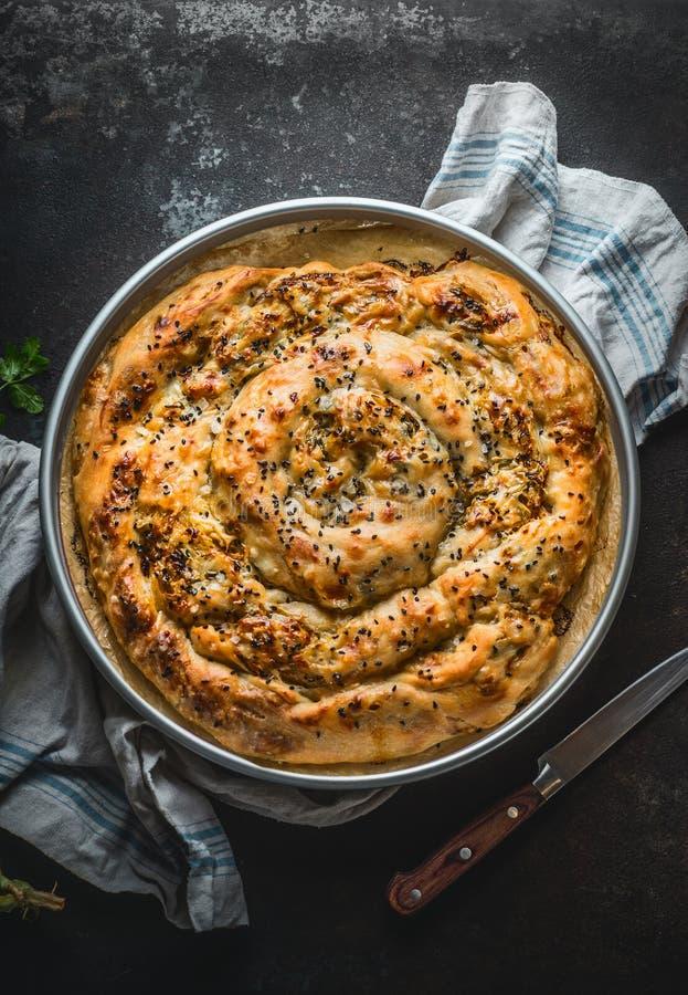 Turkish cuisine. Savory pie with Phyllo dough in baking pan. Su boregi, burek or borek on dark rustic background. Top view royalty free stock photography