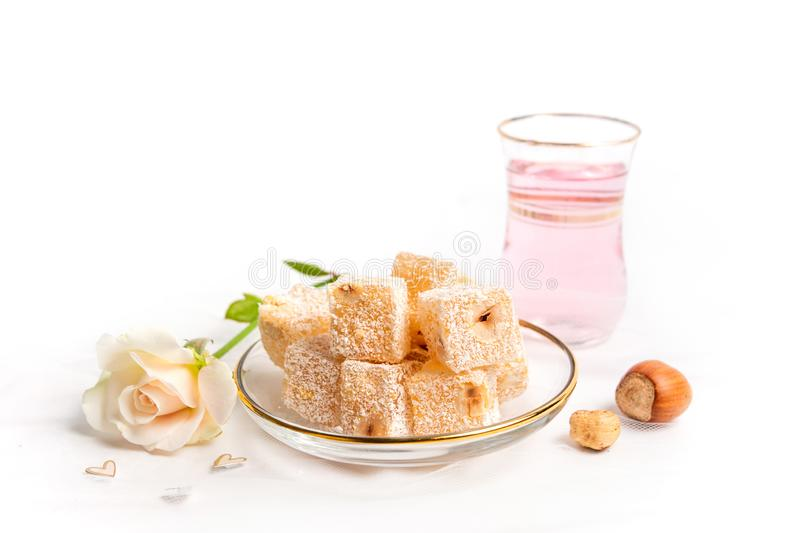 Turkish delight dessert with hazelnuts and rose tea. Turkish delight dessert with hazelnuts served with rose tea, drink, flower, white, isolated, lokum, rahat royalty free stock photo