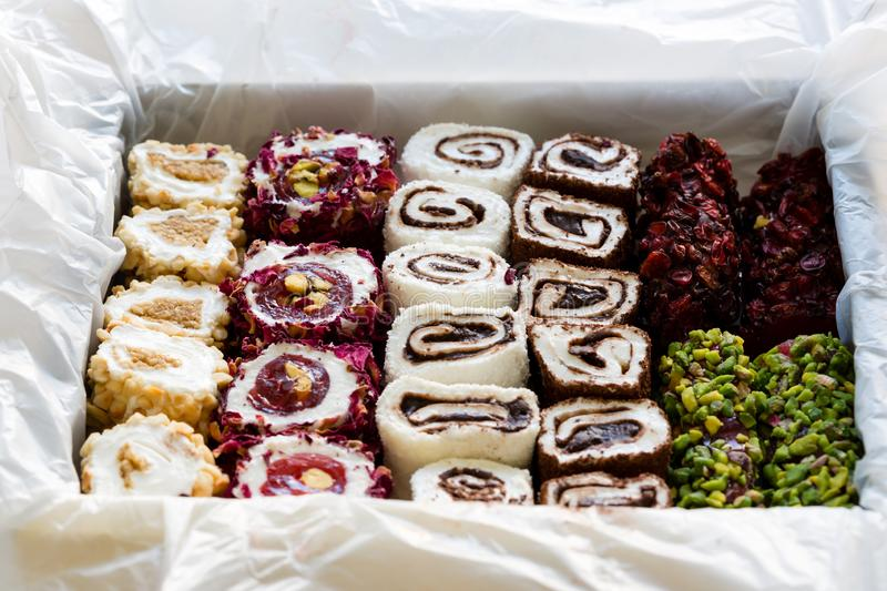 Turkish delight with nuts, pistachios, coconut, chocolate and rose leaves in the box. Rahat lokum, traditional Turkish sweets. royalty free stock photo