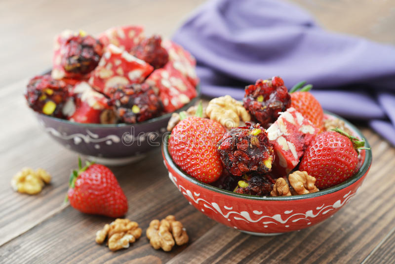 Turkish delight with nuts. And strawberry in ceramic bowl on wooden background stock photos