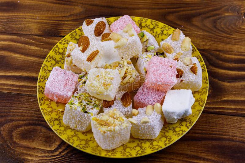 Turkish delight in a plate on wooden table. Turkish delight in a plate on a wooden table royalty free stock photos