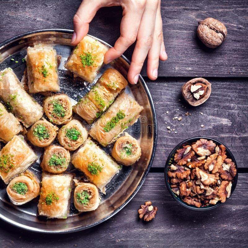 Turkish delights baklava on wooden table. Hand holding Turkish baklava near walnuts on wooden background stock photos