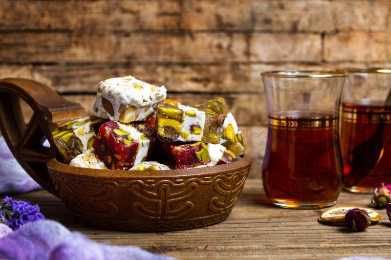 Turkish delights with pistachios and rose flower. In a bowl dessert tea snack rahat lokum table plate bunch turkey sugar nut green color background handmade royalty free stock image