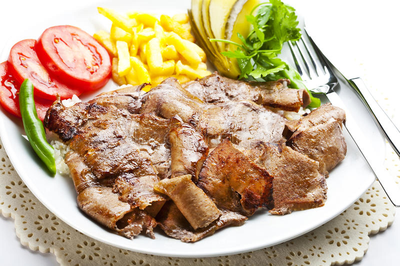 Turkish Doner Kebab. Turkish traditional food doner kebab with french fries and salads royalty free stock images
