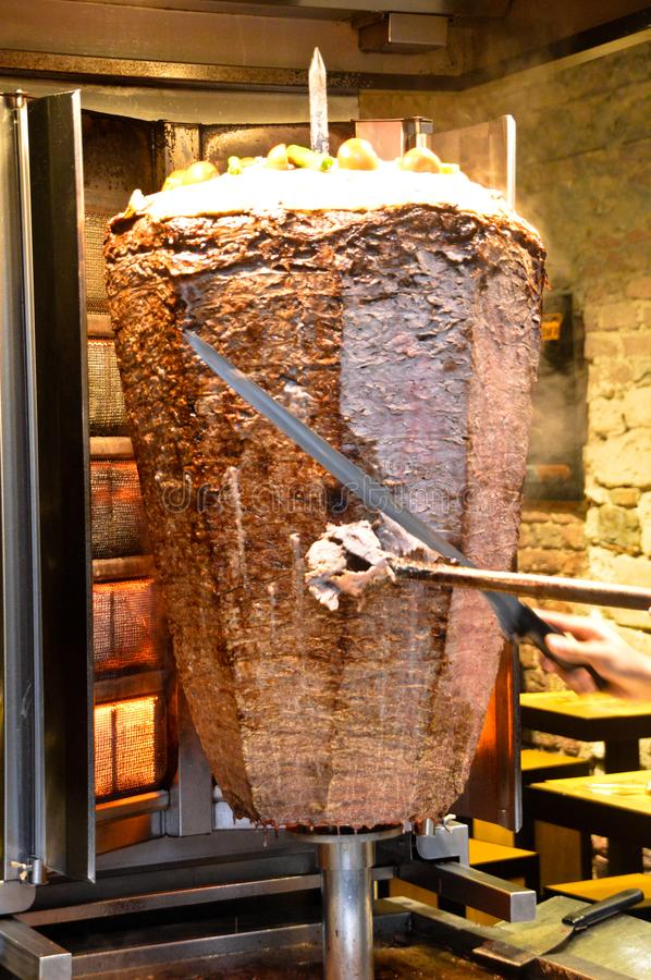 Turkish doner kebap they cut with a big knife. Delicious dishes of Turkish cuisine doner kebab they cut with a big knife royalty free stock images