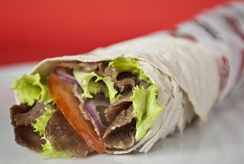 Turkish durum kebab. Traditional turkish doner kebab in lavash bread served on white plate royalty free stock photos