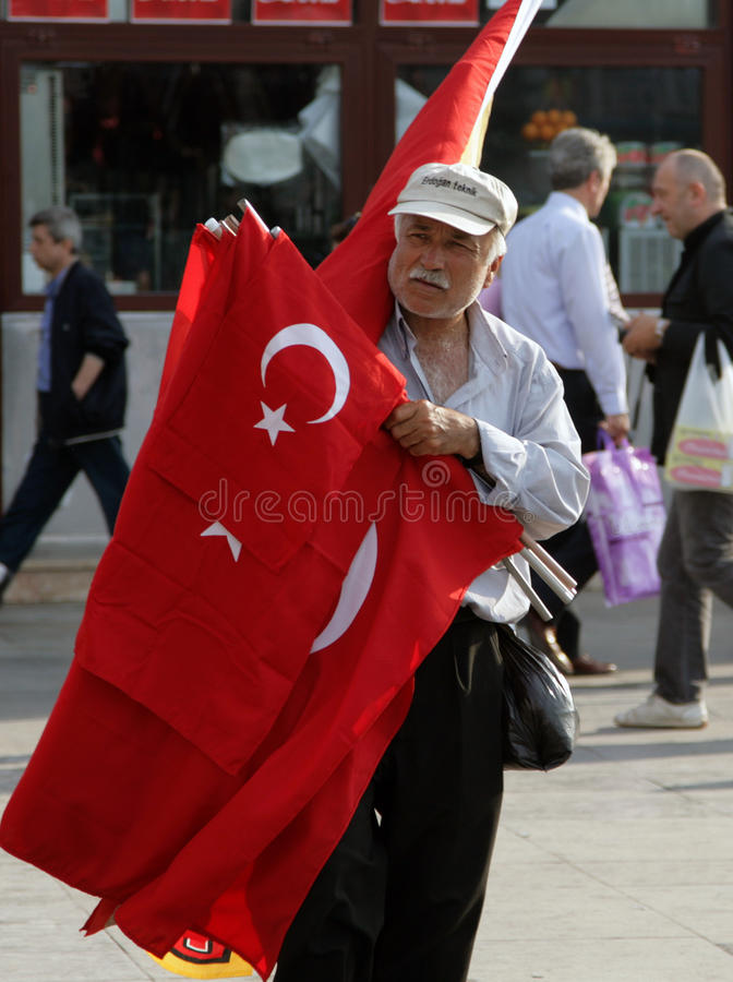 Turkish elderly man selling national flags on the square in front of the Egyptian Bazaar. ISTANBUL, TURKEY - JUN 29, 2008: Turkish elderly man selling national royalty free stock images