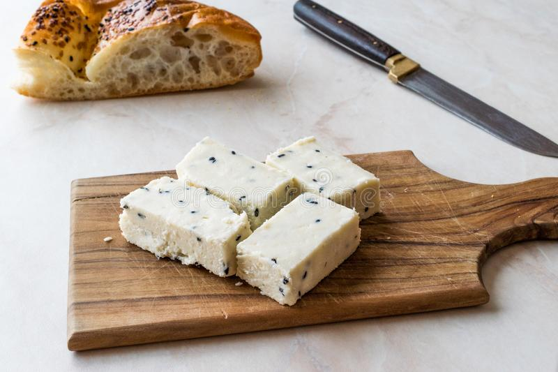 Turkish Feta Cheese with Black Cumin Sesame Seeds on Wooden Surface with Knife. royalty free stock image