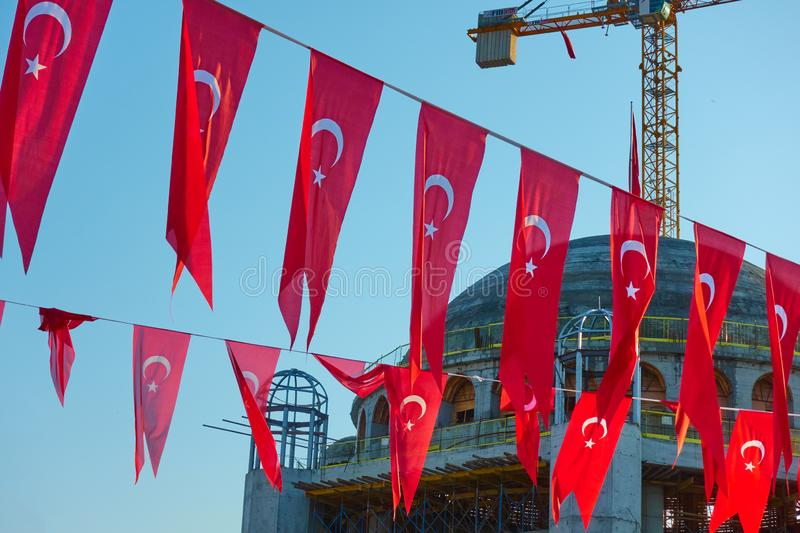 Turkish flags and construction of new mosque. Holiday turkish flags and construction of new mosque in the background, Taksim Square, Istanbul royalty free stock images
