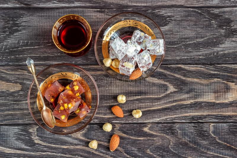 Turkish joys with different nuts is a glass of tea and a spoon. Eastern sweets. Traditional Turkish delight Rahat lokum on a. Wooden background. View from above stock photography