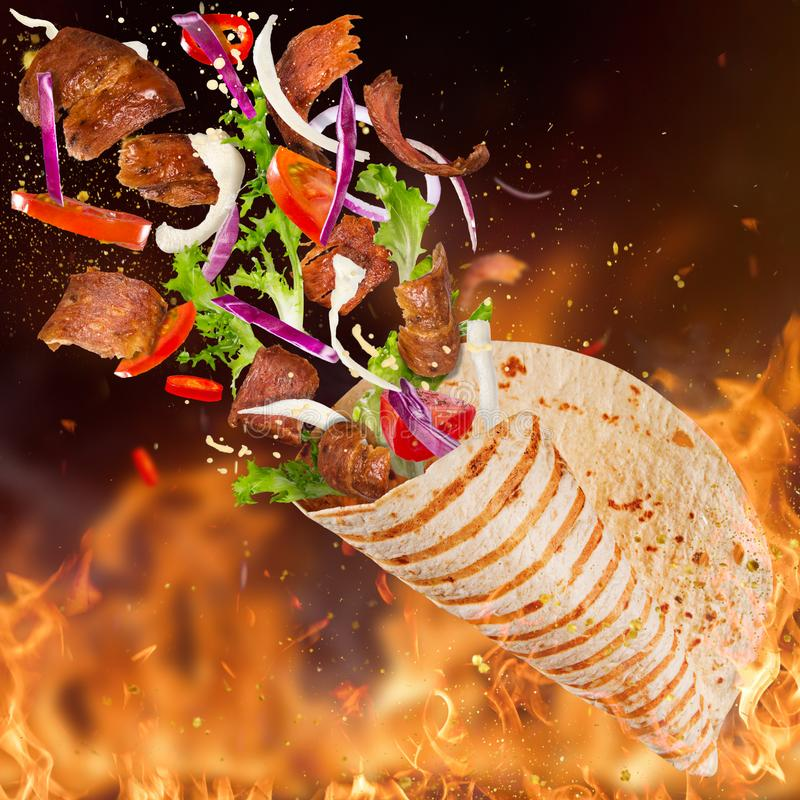 Turkish Kebab yufka with flying ingredients and flames. royalty free stock images