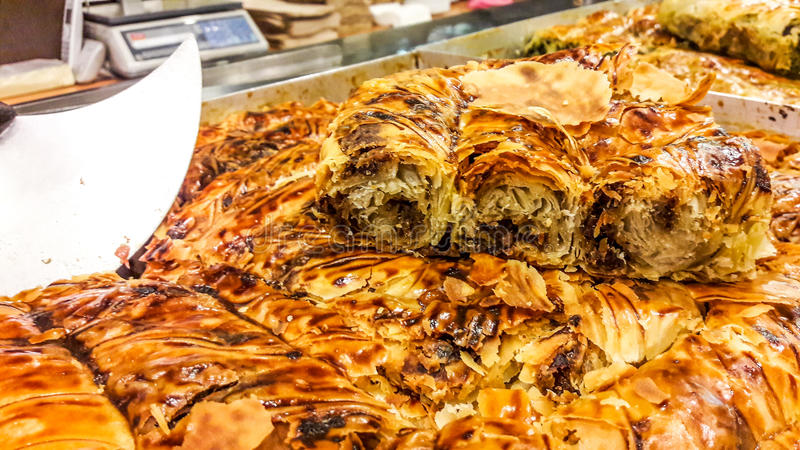Turkish Kol Boregi with minced meat and knife at patisserie showcase. Fast food stock photography