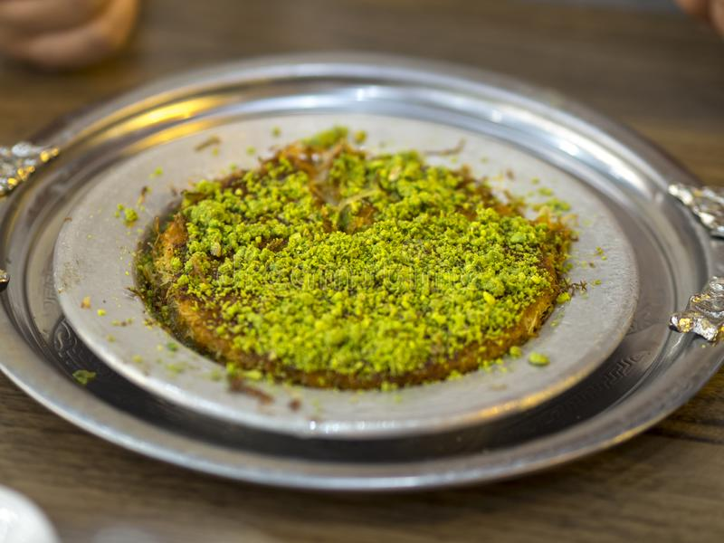 Turkish kunefe dessert in special serving dish with green pistachio.  stock image