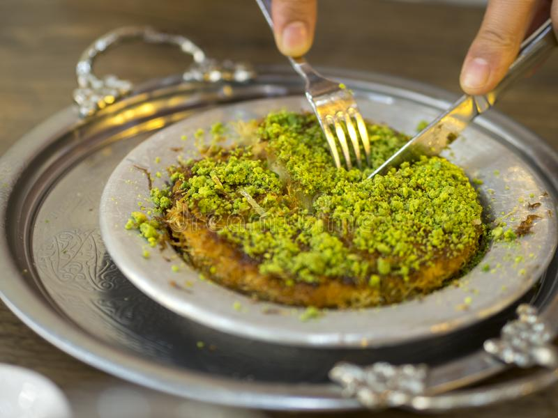 Turkish kunefe dessert in special serving dish with green pistachio.  stock photo