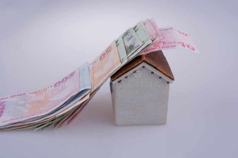 Turkish Lira banknotes on the roof of a model house. On white background royalty free stock photo
