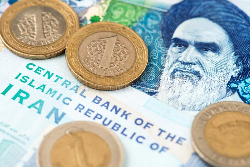 Turkish Lira Coins on Iranian Rial Currency Banknotes. Turkish Lira Coins on Iranian Rial Currency Banknotes close up image. Turkey Lira Iran Rial Money stock image