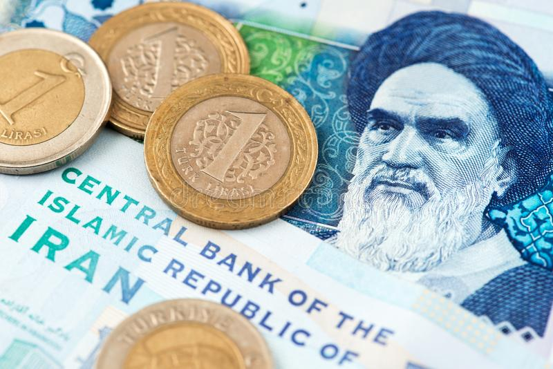 Turkish Lira Coins on Iranian Rial Currency Banknotes. Turkish Lira Coins on Iranian Rial Currency Banknotes close up image. Turkey Lira Iran Rial Money stock photo