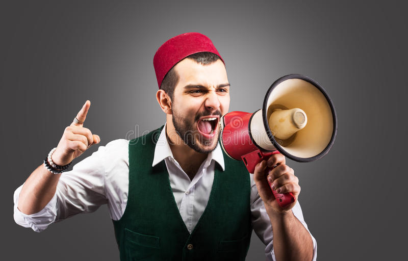 Turkish man with a megaphone. Funny portrait of a Turkish man shouting through the megaphone royalty free stock photos