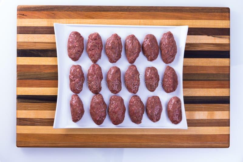 Turkish Meat Balls pronto da cucinare preparato su un bordo di legno immagini stock libere da diritti