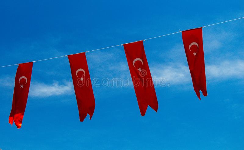 Turkish national flags with white star and moon in sky. Turkish national flags with white star and moon in blue sky royalty free stock photos