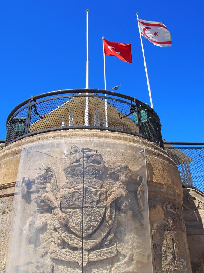 Turkish and north cyprus flags flying above and old building with the remains of a british coat of arms in nicosia. Turkish and north cyprus flags flying above royalty free stock photography