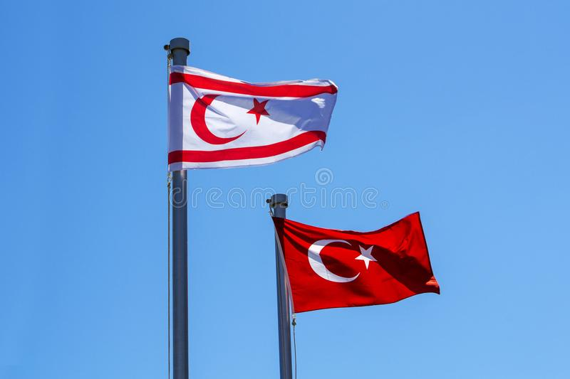 Turkish and North Cyprus flags. On blue sky background stock photo