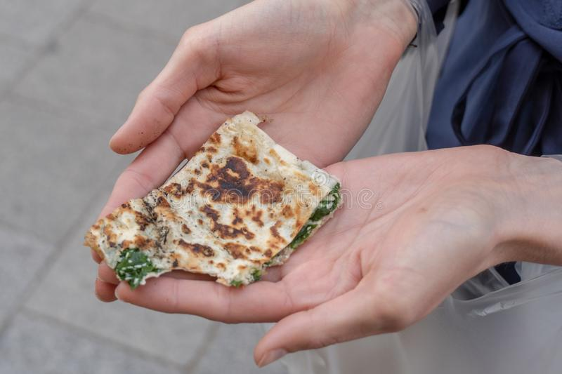 Turkish Pancake in Hand. Turkish pancake with spinach and cheese cooked on stovetop stock photo
