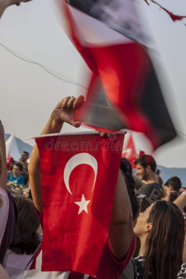 Turkish people commemorating liberation of Izmir from greeks. A crowd of turkish people is holding flags waving on the wind and happily commemorating the stock photo