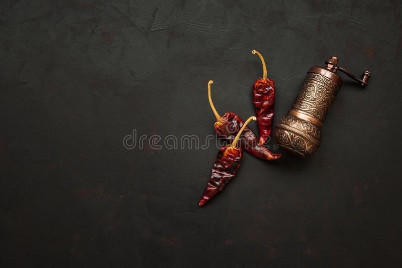 Turkish pepper mill or grinder with peppercorns of red hot chilli peppers on dark wooden background. Top view. Copy space. Turkish pepper mill or grinder with royalty free stock images