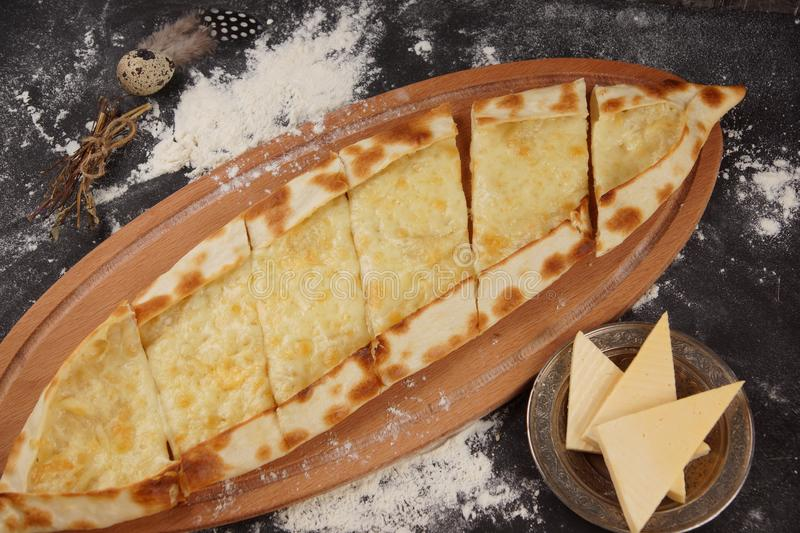 Turkish pizza is called pide. Dish with Pide with cheese on a dark table, sprinkled with flour stock photography