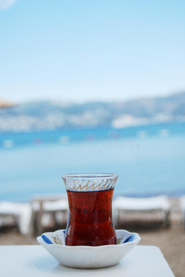 Turkish tea closeup. Traditional turkish glass with black tea on a table, tea time outside stock photography