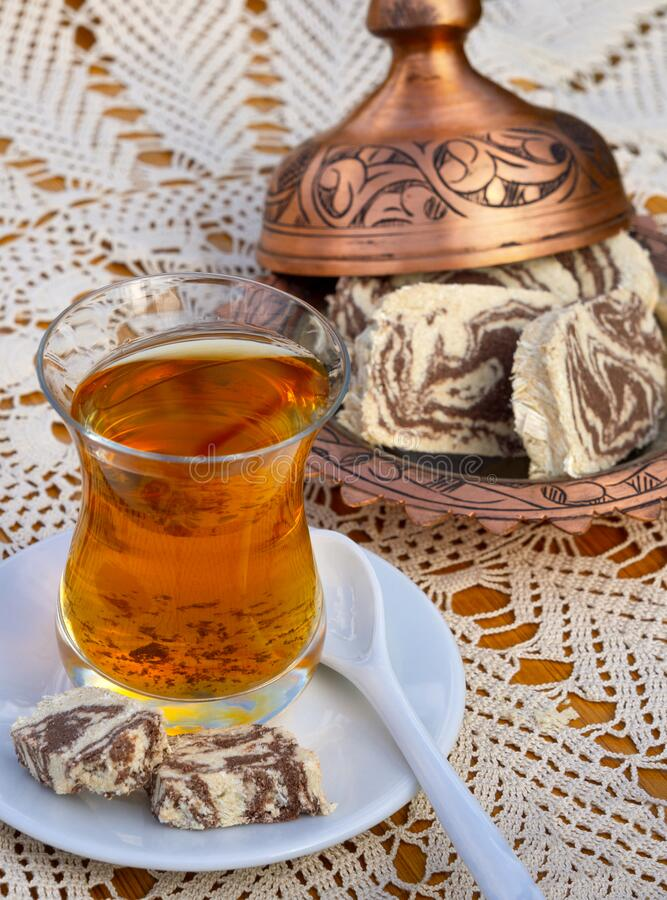 Turkish tea in a glass Cup and marble halva on a table with a handmade tablecloth and candy maker on a Sunny day. Turkish tea in a glass Cup  and marble halva on royalty free stock photos
